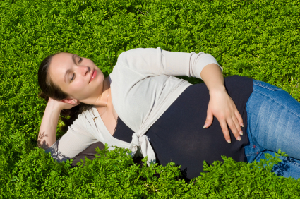 Calm pregnant woman enjoying lying in green grass